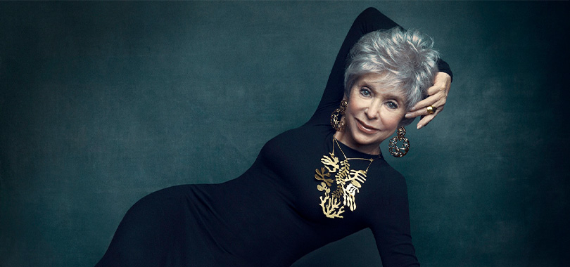 Rita Moreno lying sideways with her arm over her head
