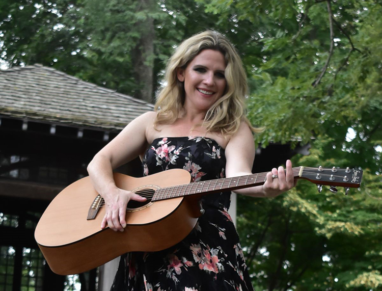 Singer-songwriter Katherine Nagy holds an acoustic guitar