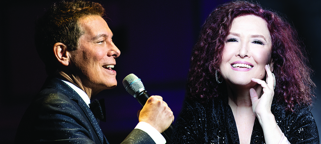 Michael Feinstein sings into a microphone as Melissa Manchester smiles at the camera.